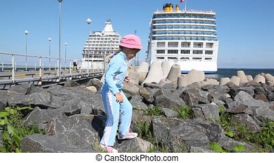 girl walks on stones at coast near mooring and passenger ships