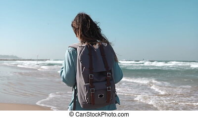 Girl walks on summer sea beach thinking about life. Freedom...