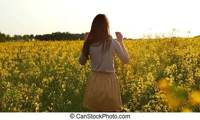 girl walks through field, straightens hair slow mo