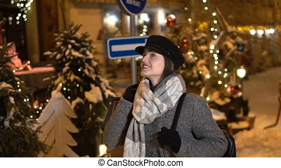 Girl Walks through Nigth Snowy City - Relaxed girl in gray...