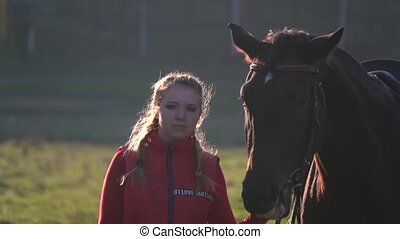 Girl walks through the meadow with a brown stallion. Slow motion