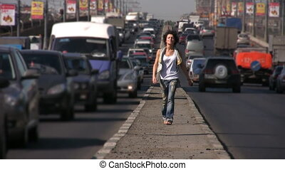 girl walks to camera on highway middle in city, blurred...