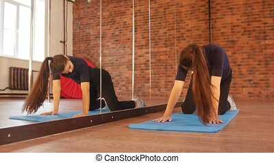 Girl warms up and doing exercises on mats in front of the mirror
