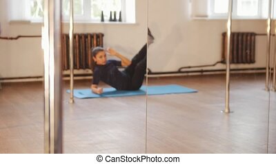 Girl warms up before training in a studio. Pole dance
