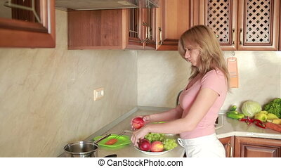 girl washes grapes. vegetables on the kitchen table. grapes...