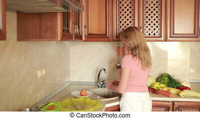 girl washes peaches. vegetables on the kitchen table....