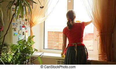 Girl washes the window, back view