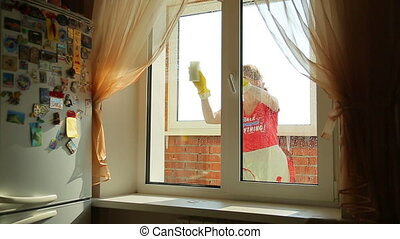Girl washes the window, front view