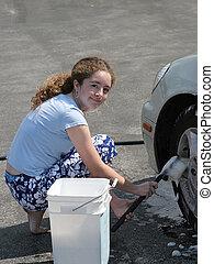 Girl Washing Car 1 - A teenaged girl scrubbing car tires...