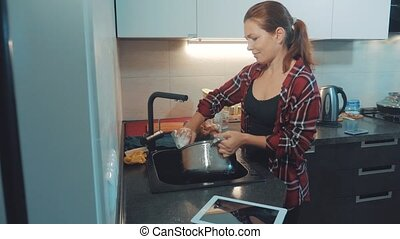 girl washing dishes in the kitchen cutting board. woman...
