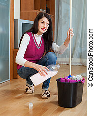 girl washing  floor with detergent at home