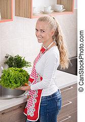 Girl washing vegetables in kitchen