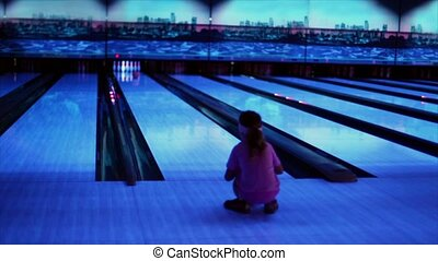 girl watch on ball trundles by bowling lane and beats skittles