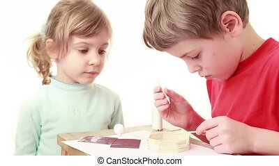 Girl watch on how boy apply glue on stick and attach to wall of match house