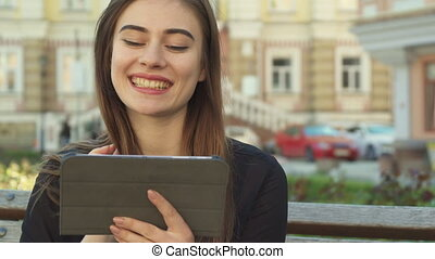 Girl watches something funny on the tablet
