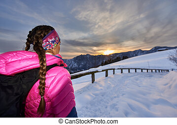 Girl watches the sunset in the mountains during a hike