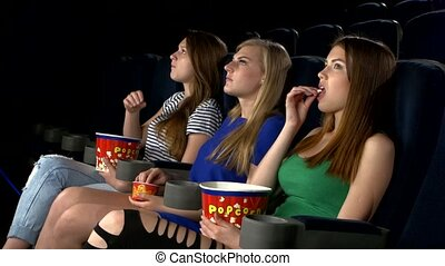 Young friends watching a film at the cinema, side view of girl, sitting in the front row. eating popcorn, watching with interest