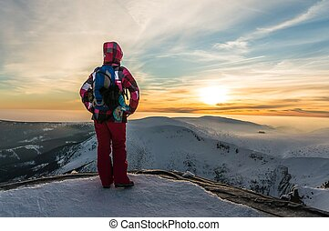 Girl watching at the sunset on the top of mountain