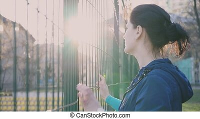 Girl watching from behind a fence, 4k, The girl looks at...