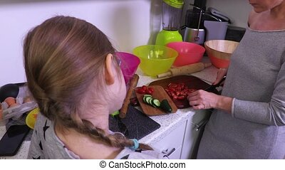 Girl watching how mother prepare salads in kitchen