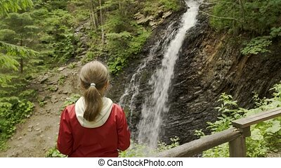 Girl watching mountain waterfall - Little girl watching...