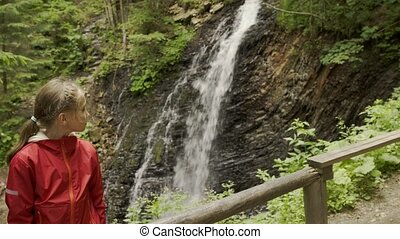 Girl watching mountain waterfall