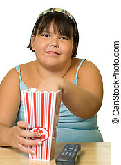 A young girl watching a movie and eating popcorn