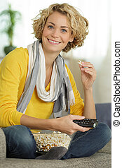 girl watching tv with popcorn at home