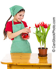 Girl watering a flowers on the desk