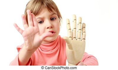 girl waves hand and wooden model of human hand - Little girl...