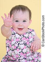girl smiling and waving hello