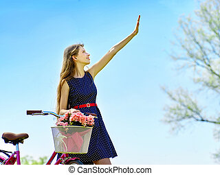 Girl wearing blue polka dots sundress rides bicycle with ...