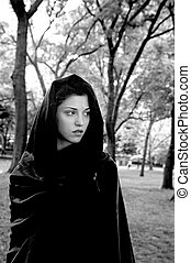 Girl wearing cloak in park. She is Jewish and was in her twenties at the time of shoot.