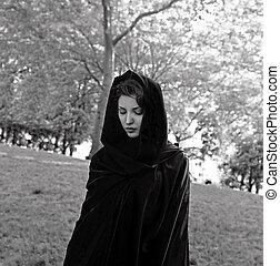 Girl wears a dark cloak in park. She is Jewish.