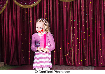 Girl Wearing Clown Make Up Holding Large Comb