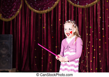 Girl Wearing Clown Make Up Holding Large Pink Comb