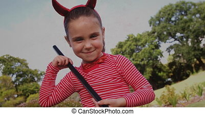 Animation of girl dressed as devil with horns holding black stick for Halloween party in a park on distressed flickering background. Halloween tradition celebration concept digital composite.