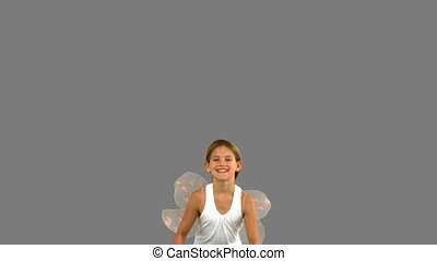 Girl wearing dragonfly wings and jumping on grey screen in...