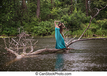 girl wearing dress standing in river near forest