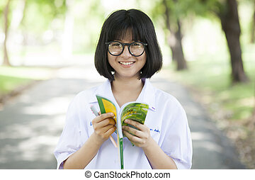 Girl wearing glasses reading book.