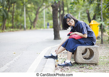 Girl wearing glasses sitting on a bench along the corridor.