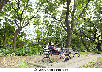 Girl wearing glasses sitting on the bench.