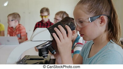 Girl wearing glasses using microscope - Close up of a ...