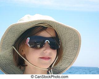 girl wearing hat at sea