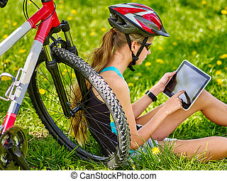 Girl wearing helmet cycling sitting near bicycle watch pc tablet.
