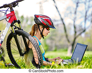Girl wearing helmet in cycling near bicycle with pc tablet.