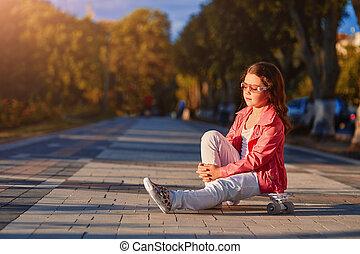 girl wearing helmet sitting on a skateboard in beautiful summer park