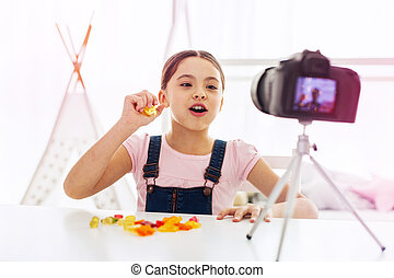 Girl wearing jeans jumpsuit sitting in front of camera eating gummy bears