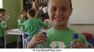 Girl wearing recycle symbol tshirt holding plastic bottles...