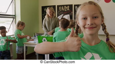 Girl wearing recycle symbol tshirt showing thumbs up - ...